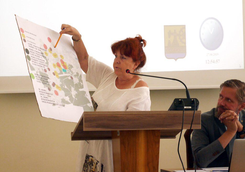 Grażyna Szczurkowska z mapą planowanych lub trwających inwestycji mieszkaniowych.