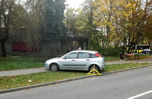 Samochód z blokadą stoi na trawniku i blokuje chodnik